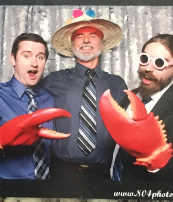 Matt, Amy's Dad, and Amy's brother being silly in a photo booth.